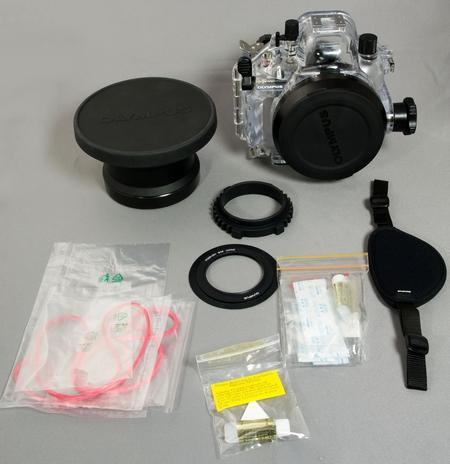 Unterwasser-Gehäuse PT-E03 mit Halteschlaufe, Objektivport PO-E05, Silikonfett, O-Ringe, Silicagel, Werkzeuge, Gummiringe für Zoom-Bedieung und Abschattungsblende für das Objektiv gegen Reflektionen.