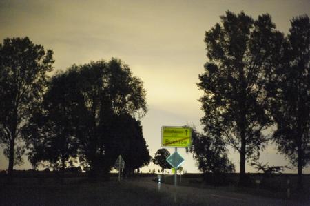 Das Ortsschild reflektiert noch das grünliche Licht einer etwa 100 m entfernten Straßenlaterne.