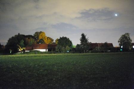 Entfernte Autodurchfahrt erleuchtet Wiese und Haus links etwas, ansonsten stockfinstere Nacht. Die Bäume sind (noch) nicht durch den Herbst verfärbt, sondern durch die Straßenbeleuchtung.
