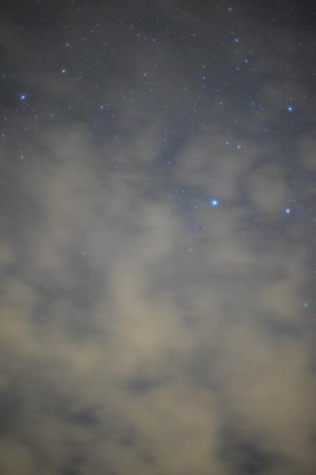 Durch die Wolken scheinende Sterne. Wegen Abgleichs auf Glühlampenlicht bläulich im Kontrast zu den gelblichen Wolken.