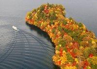 Ein Ausflugsschiff an einer herbstlich verfärbten Halbinsel auf dem Chuzenji-See bei Nikko in Japan. (Keystone / AP / Kyodo News Kenichi Murakami)