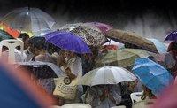 Thai werden auf der Royal Plaza in Bangkok vom Regen überrascht. Die Komposition profitiert vom schwarzen Hintergrund, der als drohendes Ungemach über die Menschen hereinbricht. (Kestone / AP / David Longstreath)