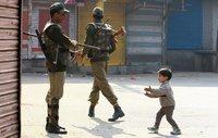 Ein kleiner Moslem-Junge spielt in Srinagar mit den Paramilitärs - und sieh aus, als ob er der Unterhändler der Demonstranten wäre. (Keystone / EPA / Faruq Khan)