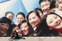 Ein Chinese ruht sich unter einem Plakat in Downtown Peking aus. (Keystone / AP / Alexander F. Yuan)