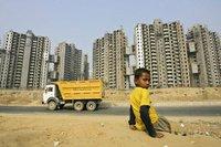 Junge vor einem Neubauviertel in Gurgaon in Indien. (Keystone / AP / Gurinder Osan)