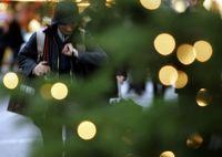 Eine Weihnachtseinkäuferin läuft in der Innenstadt von Düsseldorf an einem beleuchteten Tannenbaum vorbei. (Keystone / AP / Frank Augstein)