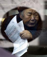 Eine chinesische Demonstrantin mit ihren Petition ans Innenministerium wird mit andern Protestierenden in einem Bus in peking abgeführt. (Keystone / AP / Andy Wong)