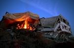 Eine palästinensische Familie am Lagerfeuer in ihrer Notunterkunft neben dem zerstörten Haus in Jabiliya im Gazastreifen. (Keystone / EPA /Jim Hollander)