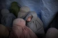 Ein Flüchtlingskind blickt über die Schulter. während Frauen in Burkas aus den Stammesgebieten in Pakistan sich in einem Flüchtlingslager bei Peschawar registrieren. (Keystone / AP / Emilio Morenatti)