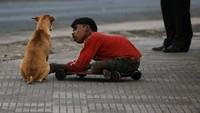 Der behinderte Krabben-Händler Sayeed Mohammed im Zwiegespräch mit einem Streunenden Hund namens Rani bei den Docks von Mumbai, Indien. (Keystone / AP / Gautam Singh)