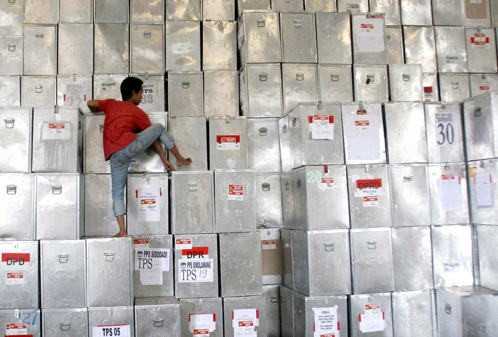 Ein Indonesischer Arbeiter ordnet Wahlurnen. (Keystone)