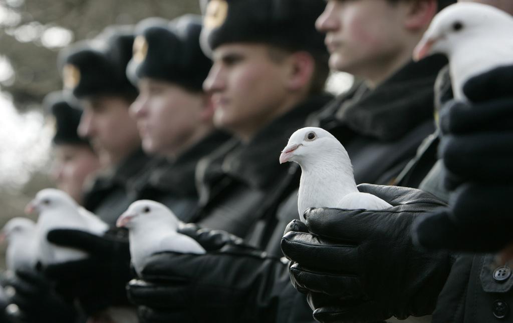 Absolventen der weißrussischen Polizeischule stehen zur Abschlusszeremonie mit weißen Tauben in der Hand bereit, diese fliegen zu lassen. (Keystone)