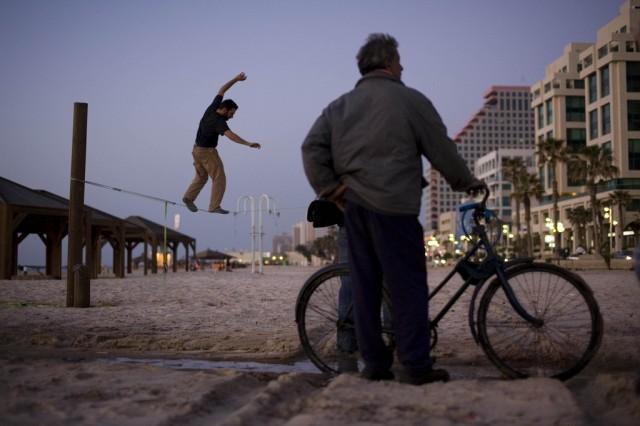 Ein Seiltänzer unterhält sich und einen Passanten am Strand von Tel Aviv in Israel. (keystone)