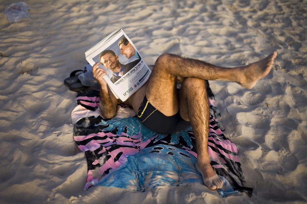Ein Israeli liest eine Zeitschrift am Strand in Tel Aviv (keystone)