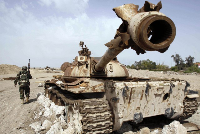 Irakischer Soldat vor zerstörtem Panzer (keystone)