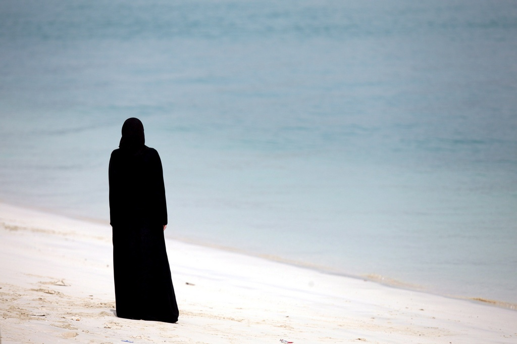 Frau am Strand von Abu Dhabi (Keystone)