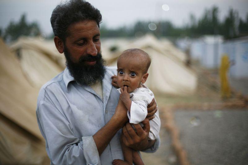 Vater mit Baby im Flüchtlingslager (keystone )