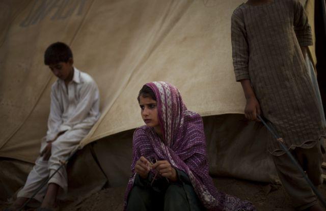 Ein Flüchtlingsmädchen sitzt neben seinem Zelt in Swabi (keystone)