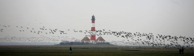 Menschen spazieren an der Nordsee beim Leuchtturm (keystone)