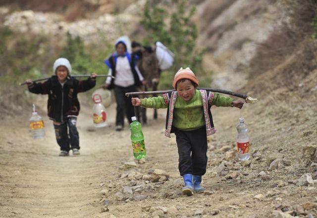 Zong Anjing, 6 Jahre, bringt Wasser von einer Bergquelle in sein Dorf.