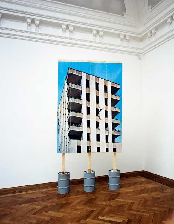 Stefan Burger - Sprung ins Leere unter Begutachtung einer Expertenkommission, 2006, Inkjet-Print auf Bretterwand, Beton, Metallfässer, 400 x 200 x 80 cm © Stefan Burger