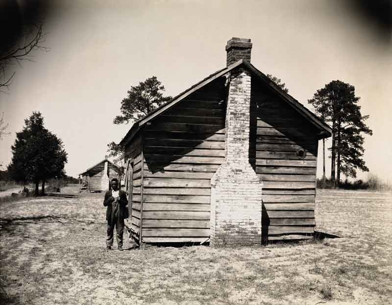 Walker Evans: Man Posing for Picture in Front of Wooden House, 1936 