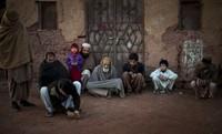 Ein Junge spielt im Kreis der Männer seiner Familie mit Murmeln. Islamabad, Pakistan, Samstag. (Keystone / AP / Emilio Morenatti)