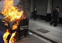 Passanten gehen an einem brennenden Container vorbei, nachdem die spanische Polizei in Bilbao eine Demonstration der baskischen Demokratiepartei aufgelöst hat (Keystone / AP / Alvaro Barrientos)