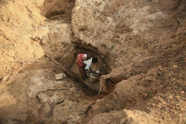 Mutter mit Kind holt Wasser (keystone)