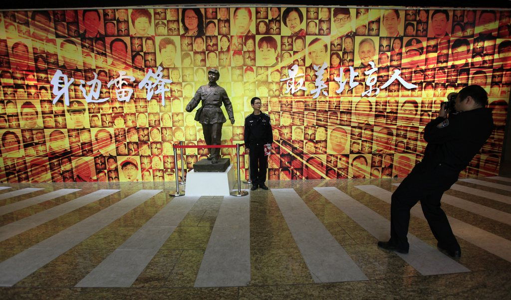 Ein Besucher posiert vor einer Statue von Lei Feng in der Ausstellung «Learn from Lei Feng Day» im Beijing World Art Museum - Beijing, China. (Keystone/EPA/How Hwee Young)