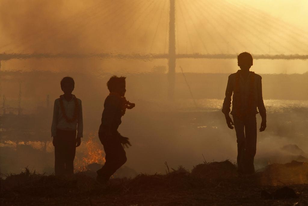 Kinder spielen im Sonnenuntergang am Zusammenfluss der heiligen Ströme Indiens  (AP Photo/ Rajesh Kumar Singh)