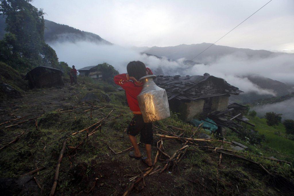 Ein Kind trägt Wasser am frühen Morgen, Nepal EPA/NARENDRA SHRESTHA