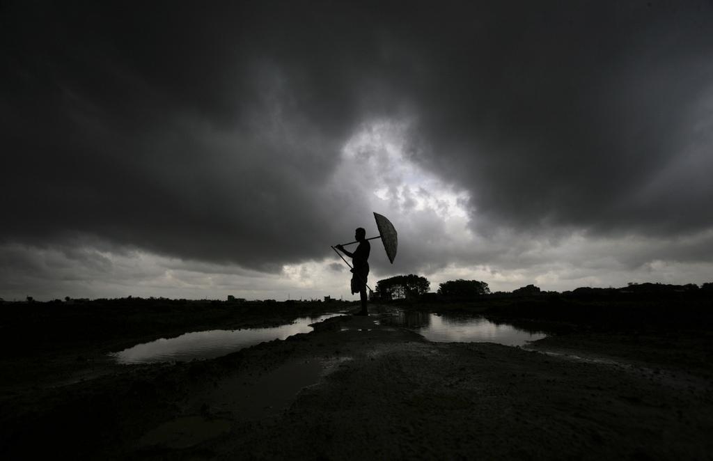 Ein Mann mit Regenschirm in Bhubaneswar, Indien (Keystone/AP Photo/Biswaranjan Rout)