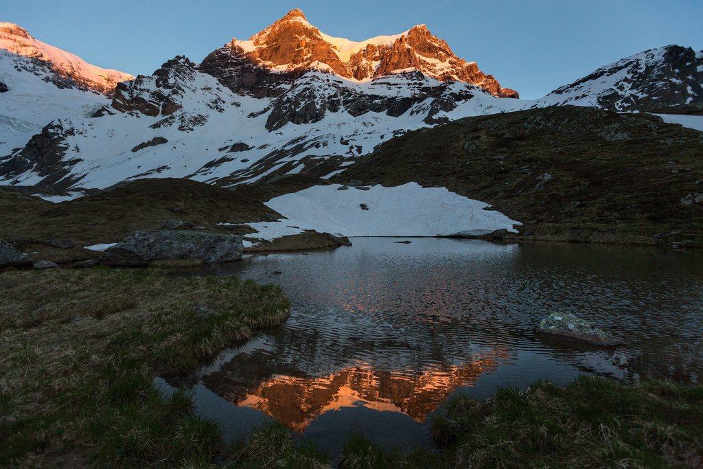 Die ersten Sonnenstrahlen erhellen den Grat des Piz Urlaun und des Toedi oberhalb Linthal im Glarnerland (KEYSTONE/Arno Balzarini)