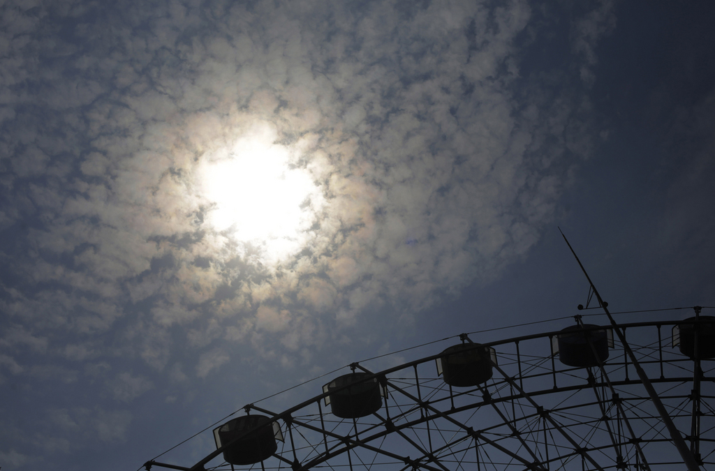 Sommersonne über einem Riesenrad in Shanghai China (AP Photo/Eugene Hoshiko)