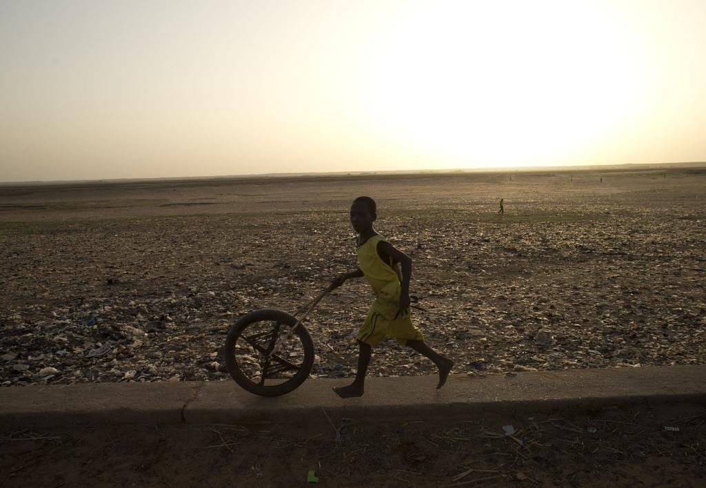 Ein Junge mit einem Reifen  in Gao, Mali (AP Photo/Rebecca Blackwell)