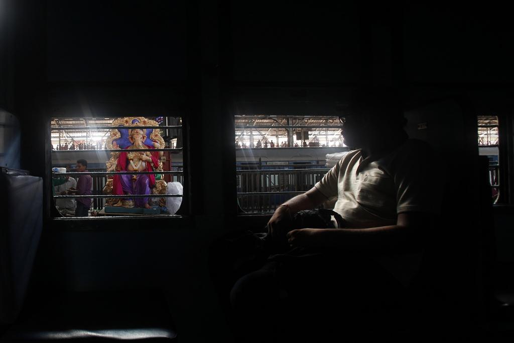 Zugreisender und Skulptur des Hindu-Gottes Ganesh, Mumbai, Indien (AP Photo/Rafiq Maqbool)