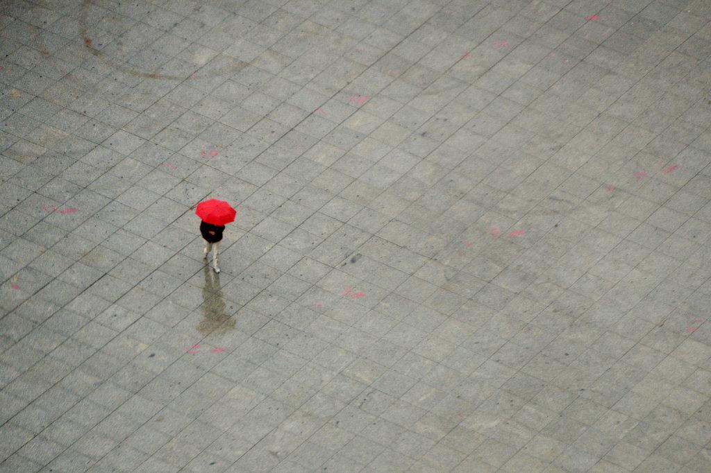 Eine Passantin im Berliner Regen (Keystone/dpa/Maurizio Gambarini)