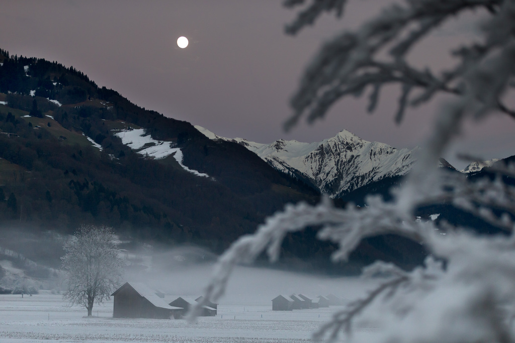Der Mond erhellt die nebelverhangene Ebene in den Schwellenen in Gruesch im Vorderprättigau CH  (KEYSTONE/Arno Balzarini)
