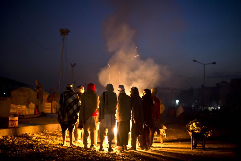 Pakistanische Tagelöhner wärmen sich am frühen Morgen, Islamabad  (AP Photo/Muhammed Muheisen)