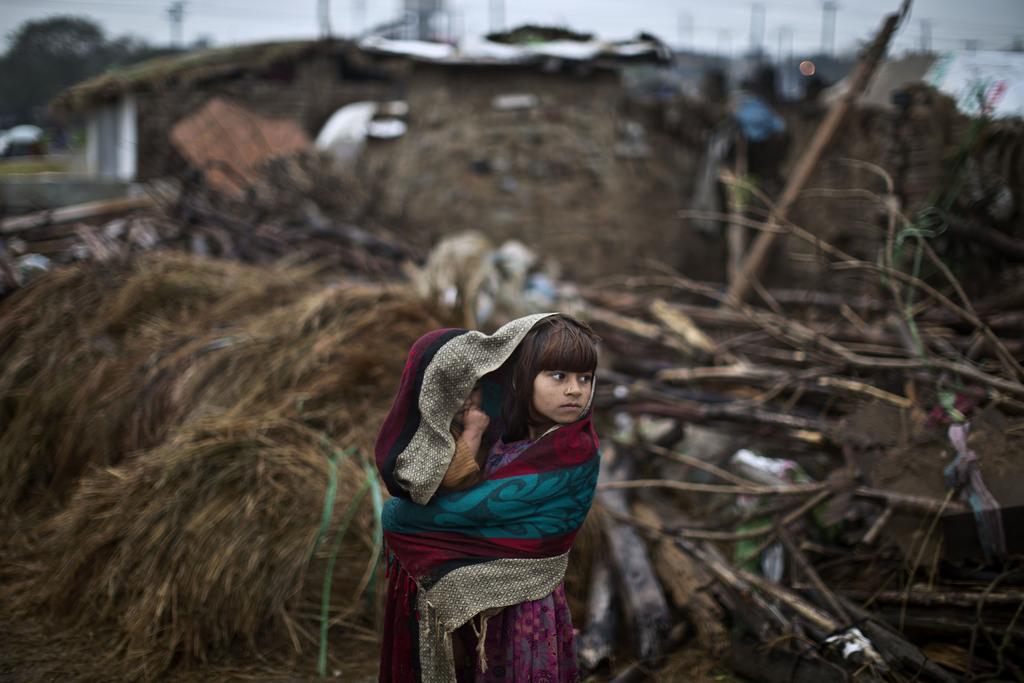 Mädchen schützt sich und ihren kleinen Bruder vor Regen, Islamabad, Pakistan (AP Photo/Muhammed Muheisen)