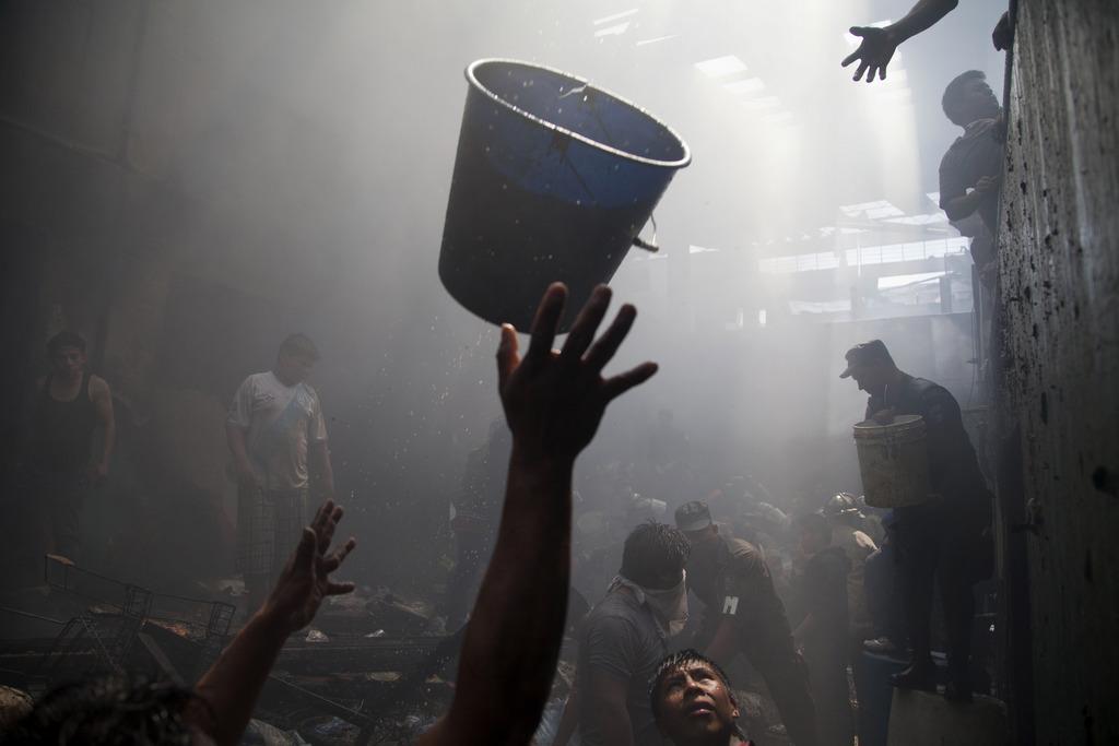 Wassereimer zum Löschen bei einem Brand in einem Markt in Guatemala-Stadt,  (AP Photo/Moises Castillo)