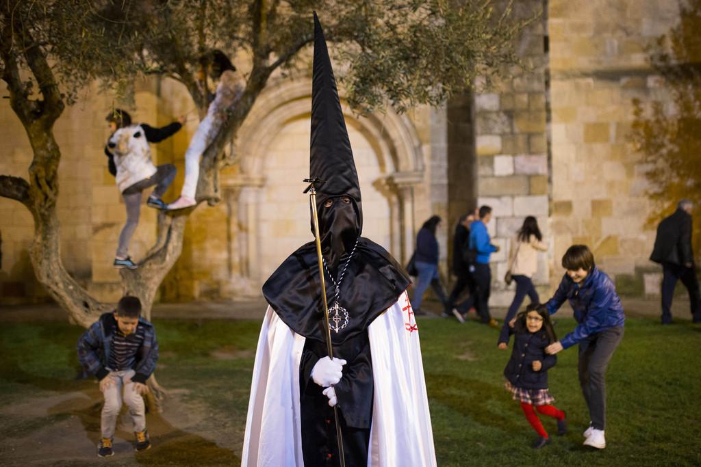 Büßer während der Karwoche - Semana Santa - in Zamora, Spanien, im Hintergrund spielende Kinder  (AP Photo/Andres Kudacki)