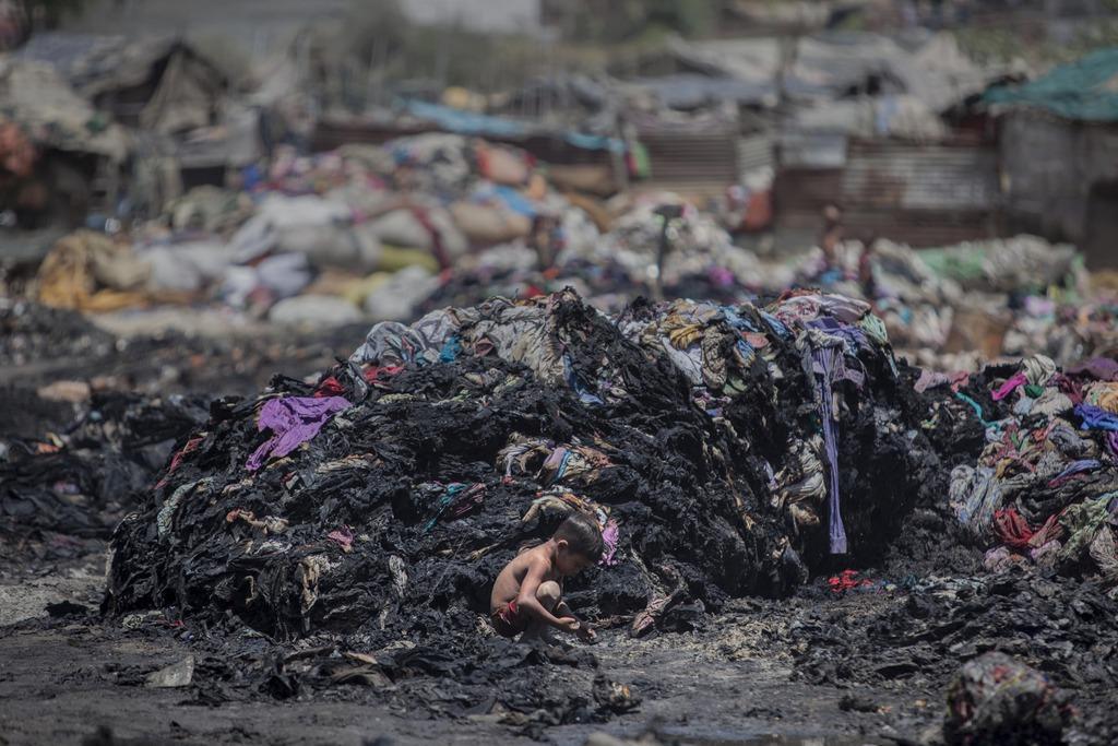 Nach einem verheerenden Brand in einem Slum sucht ein Junge nach Überbleibseln, außerhalb von Neu Delhi, Indien  (AP Photo/Tsering Topgyal)