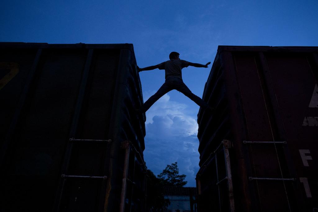 Mann klettert zwischen Zugwaggons, Arriaga, Mexiko (AP Photo/Rebecca Blackwell)