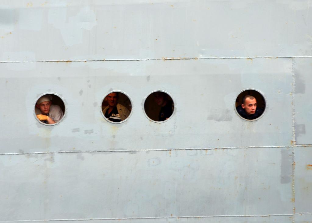 Russische Seeleute schauen aus Bullaugen, St. Nazaire F (AP Photo/ Laetitia Notarianni)
