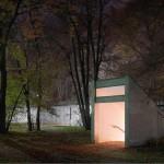 Die BND-Zentrale In Pullach. Neuer Geländeteil, Eingang Fußgängertunnel. Als das Gelände bebaut wurde, waren die Bäume noch nicht vorhanden. Heute scheint es, als verlaufe eine mit NATO-Draht gesicherte und beleuchtete Stahlwand quer durch den Wald. Der Eingang zum Fußgängertunnel ist beleuchtet, eine künstlich angelegte Höhle inmitten der Idylle.© Martin Schlüter / Kunstfoyer München