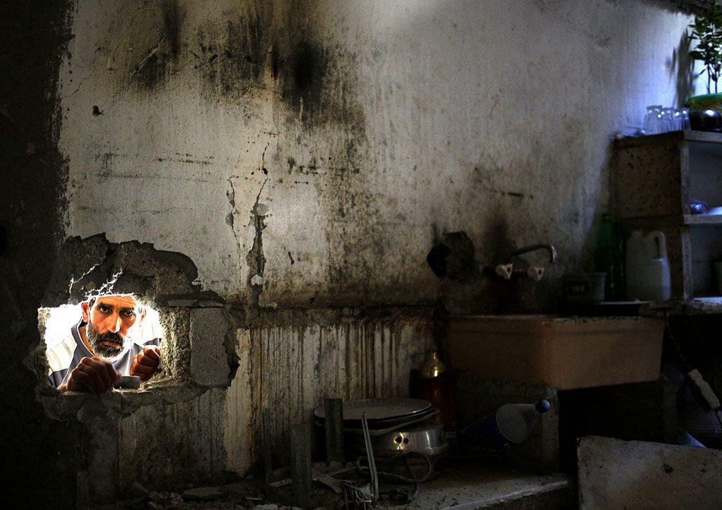 Ein Palästinenser inspiziert ein zerstörtes Haus in Gaza Stadt (Keystone/EPA/Mohammed Saber)