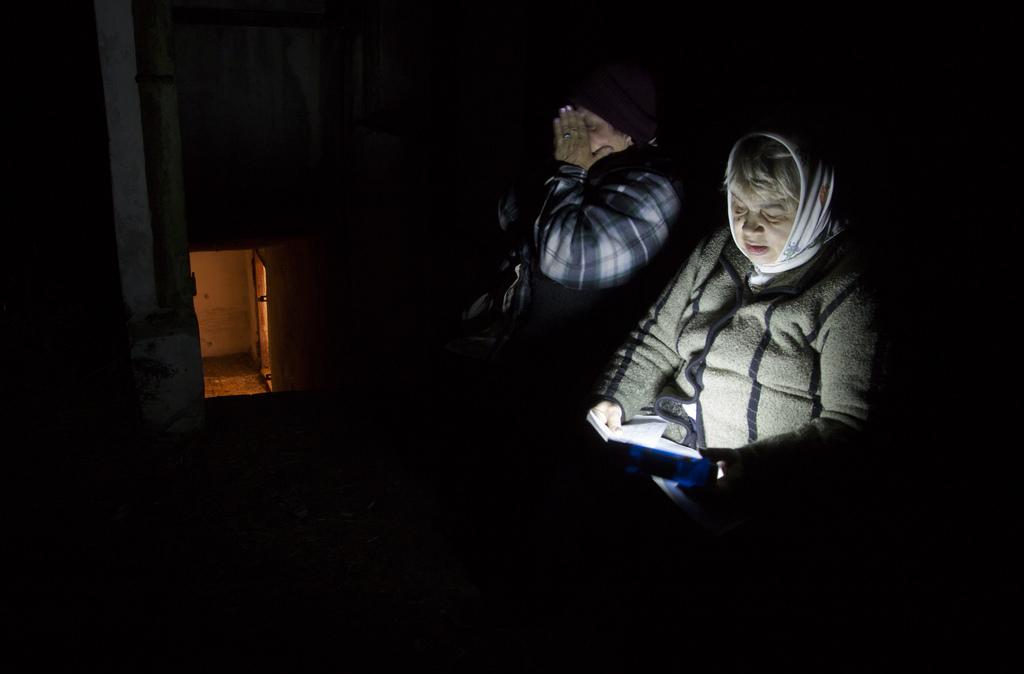 Frauen vor dem Eingang zu einem Schutzbunker, Ostukraine  (AP Photo/Dmitry Lovetsky)