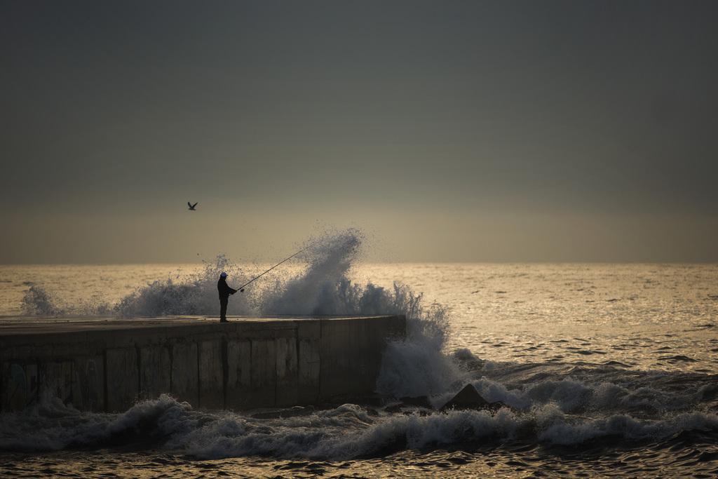 Angler am aufgewühlten Meer nach Sonnenuntergang, Barcelona, Spanien  (AP Photo/Emilio Morenatti)